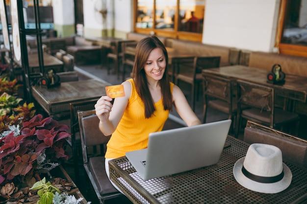 Femme au café de la rue en plein air assis à table avec un ordinateur portable moderne, tient en main une carte de crédit bancaire