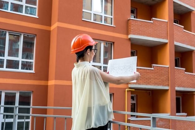 Femme au casque comparant le plan et le bâtiment construit