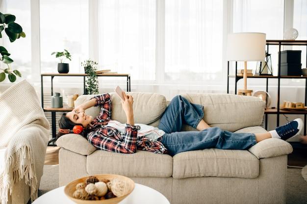 Femme au casque, écouter de la musique sur le canapé.