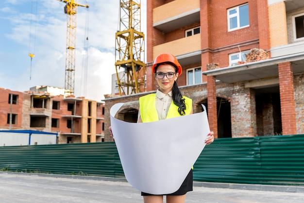 Femme au casque à la recherche de dessin au chantier de construction