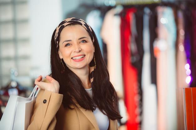 Femme au centre commercial. femme heureuse avec des sacs à provisions appréciant le processus d'achat. concept d'accro du shopping