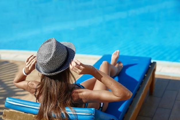 Femme au chapeau allongé sur une chaise longue près de la piscine