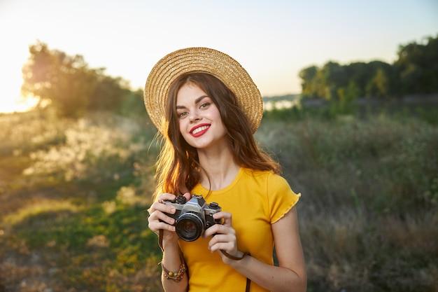 Femme au chapeau et un appareil photo