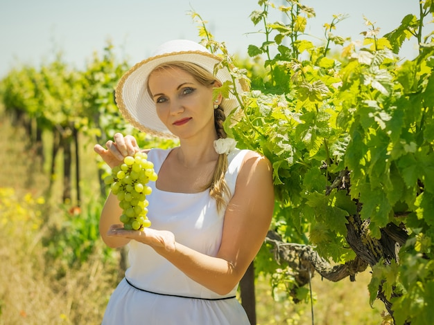 La femme au chapeau blanc montre une grappe de raisin vert mûr.