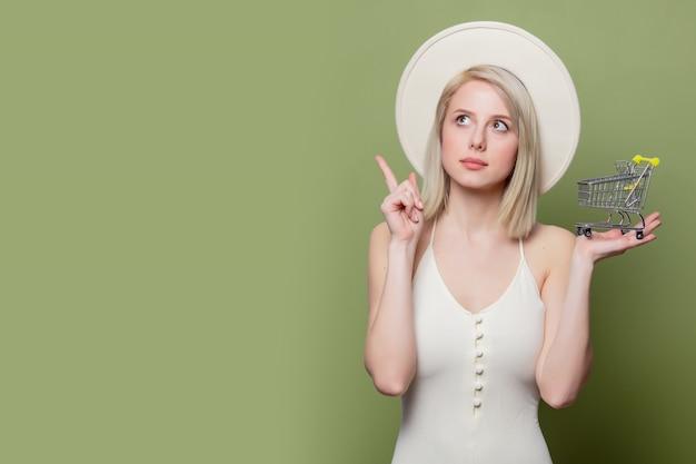 Femme au chapeau blanc et robe avec petit panier