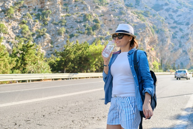 Femme au chapeau avec une bouteille d'eau dans les montagnes sur l'autoroute, faisant de l'auto-stop, arrêtant le bus, avec espace de copie. nature, route, tourisme, voyage, aventure, fond de concept de voyage sur la route