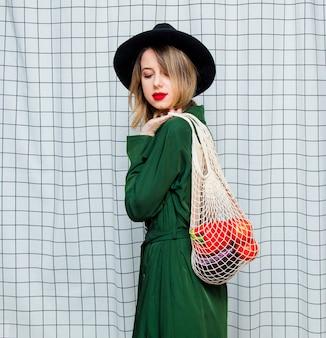 Femme au chapeau et cape verte dans le style des années 90 avec sac en filet