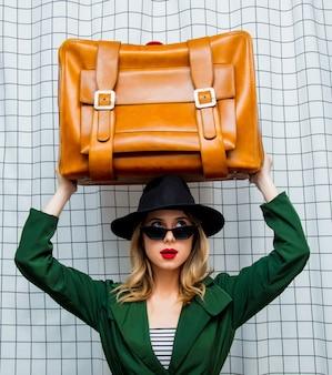 Femme au chapeau et cape verte dans le style des années 90 avec valise de voyage