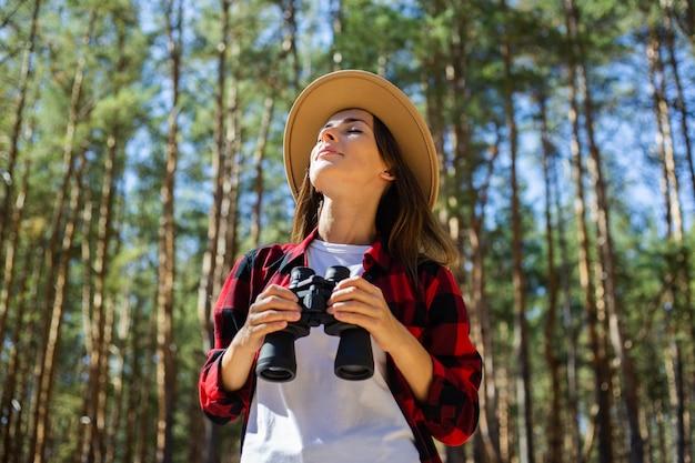 Femme au chapeau et chemise à carreaux rouge tenant des jumelles dans la forêt.