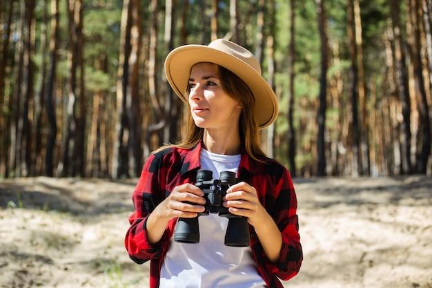 Femme au chapeau et chemise à carreaux rouge tenant des jumelles sur fond de forêt.
