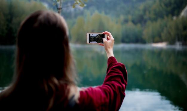 Femme au chapeau et une chemise rouge avec un téléphone portable près du lac
