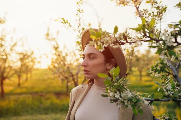 Femme au chapeau dans un jardin printanier où les arbres fleurissent au coucher du soleil