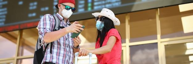 Femme au chapeau debout avec l'homme sur la gare et le calendrier d'étude