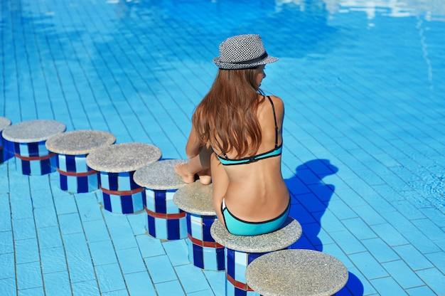Femme au chapeau est assise au bord de la pierre au milieu de la piscine. bel hôtel exotique pour des vacances relaxantes