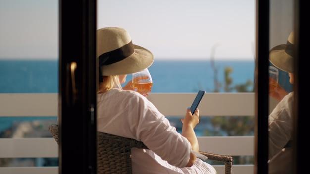 Femme au chapeau d'été se détendre dans un fauteuil sur le balcon donnant sur la mer. elle boit du vin blanc et navigue sur le web sur un téléphone intelligent