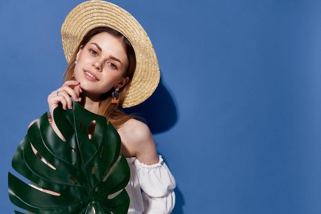 Femme au chapeau feuille de palmier dans les mains mur bleu exotique de luxe.