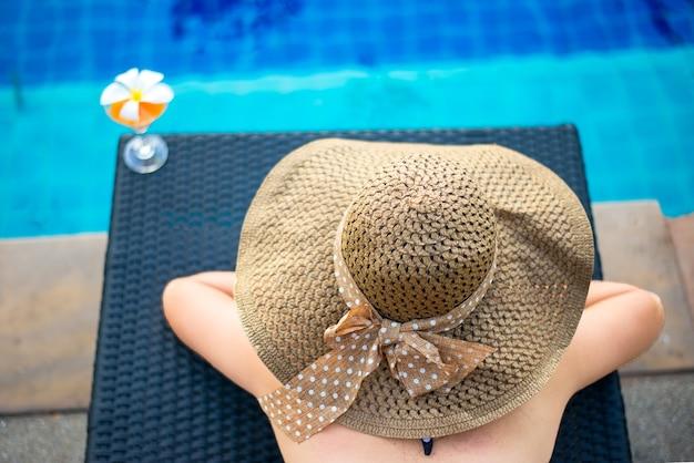 Femme au chapeau grand reposant sur la piscine