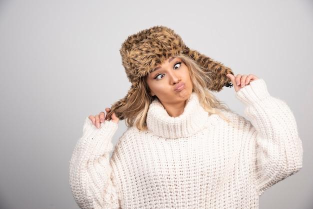 Femme au chapeau d'hiver faisant des visages ludiques.