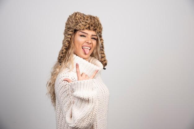 Femme au chapeau d'hiver sortant sa langue.