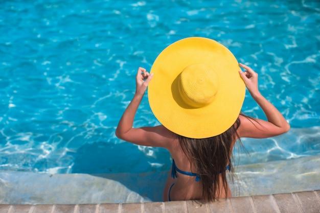 Femme au chapeau jaune se détendre à la piscine