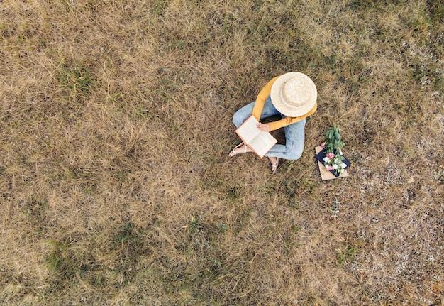 Une femme au chapeau lisant un livre - une vue de dessus
