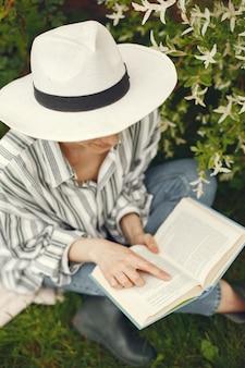 Femme au chapeau avec un livre dans un jardin