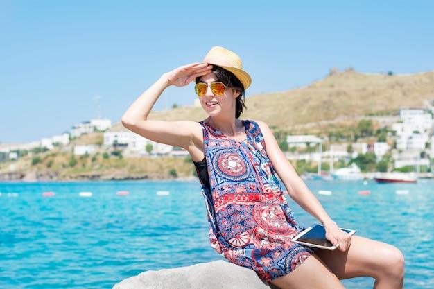 Femme au chapeau et des lunettes de soleil buvard le soleil avec la main