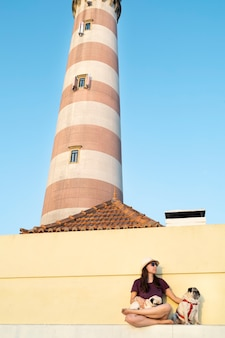 Femme au chapeau et lunettes de soleil avec ses chiens au coucher du soleil à côté du phare d'aveiro au portugal