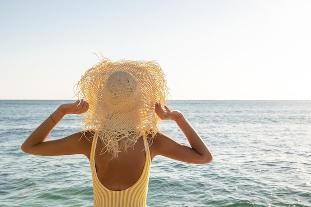 Femme au chapeau sur la mer
