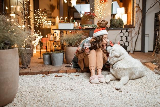 Femme au chapeau de noël célébrant avec son chien mignon les vacances du nouvel an, assis ensemble sur la terrasse joliment décorée à la maison