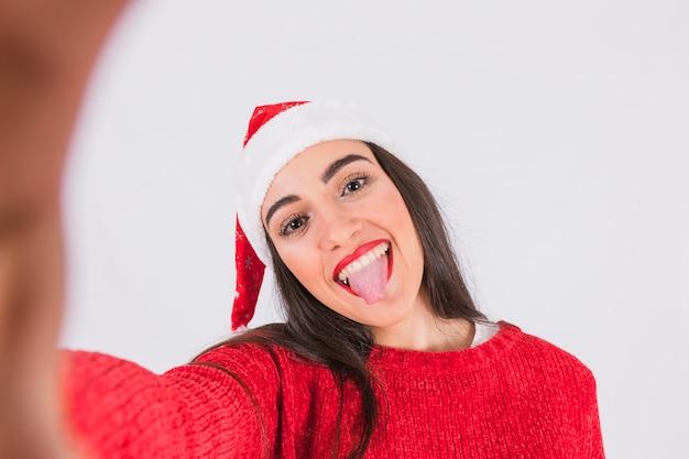 Femme au chapeau de noël montrant la langue dehors