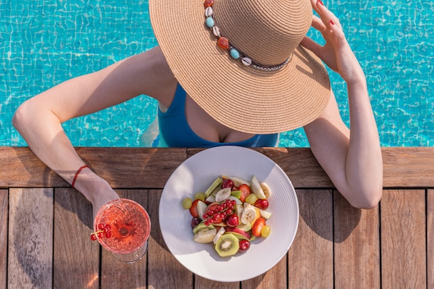 Femme au chapeau de paille et bikini aux fruits rouges près de la piscine