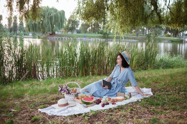 Une femme au chapeau de paille est assise sur un pique-nique dans un parc au bord d'une rivière