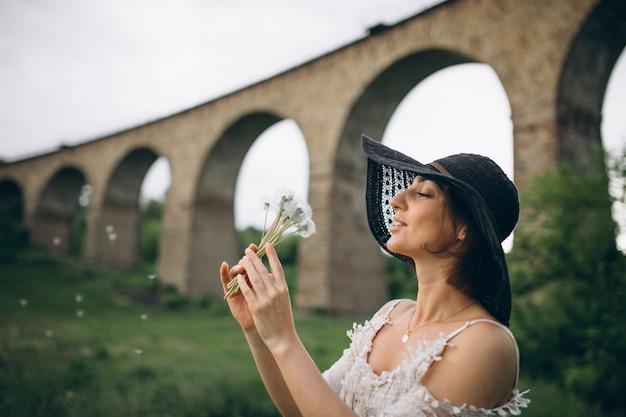 Femme au chapeau par le pont de chemin de fer avec pissenlit