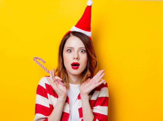 Femme au chapeau de père noël avec une canne en bonbon
