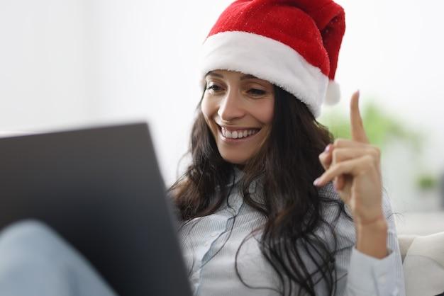 Femme au chapeau de père noël sourit tient les pouces vers le haut et se penche sur l'ordinateur portable.