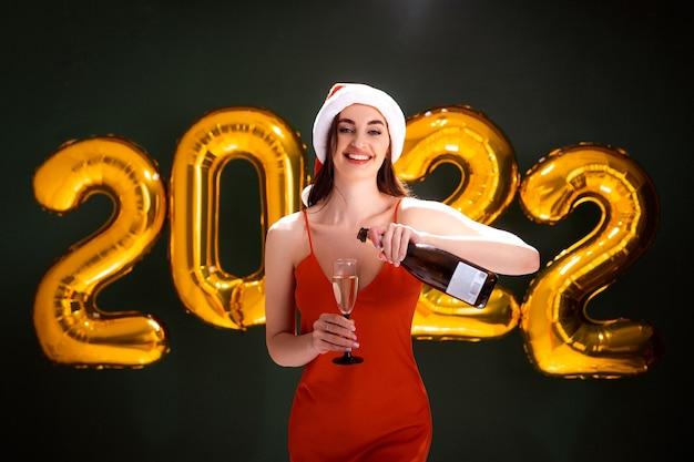 Femme au chapeau de père noël verser des ballons à air champagne bonne année célébration fête de vacances