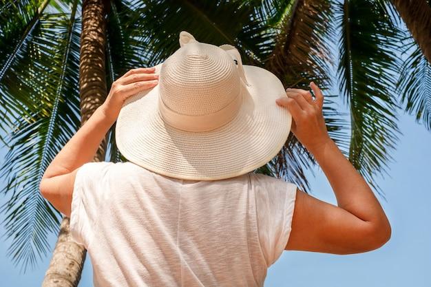 Femme au chapeau en regardant les palmiers. fille en robe boule et chapeau sur fond de feuilles de palmier