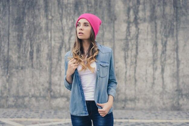 Femme au chapeau rose jeans chemise fond mur gris