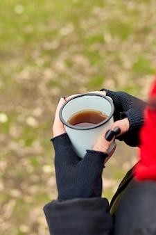 Femme au chapeau rouge et écharpe, buvant du thé dans une tasse en métal en plein air, concept de voyage, paysage d'arrière-plan d'automne.
