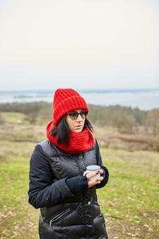 Femme au chapeau rouge et écharpe, buvant du thé dans une tasse en métal en plein air
