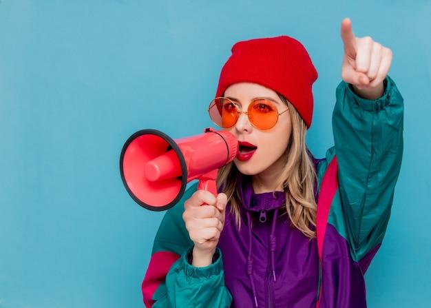 Femme au chapeau rouge, lunettes de soleil et costume des années 90 avec haut-parleur