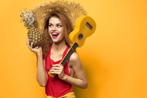 Femme au chapeau rouge ukulélé dans les mains mode de vie été t-shirt rouge mur jaune.