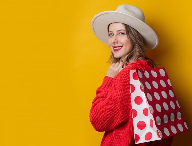 Femme au chapeau et sacs à provisions
