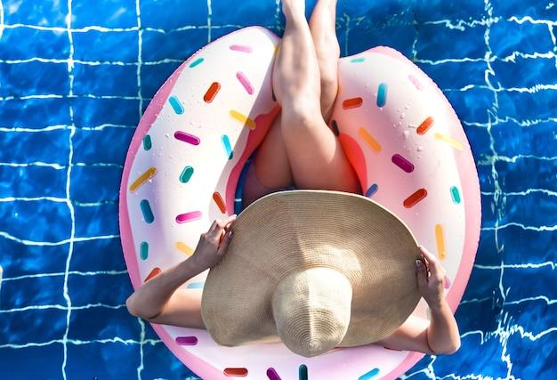 Une femme au chapeau se détend sur un cercle gonflable dans la piscine.