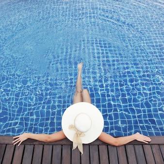 Femme au chapeau se détendre à la piscine