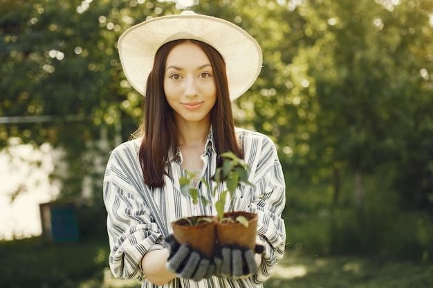 Femme au chapeau tenant des pots de fleurs