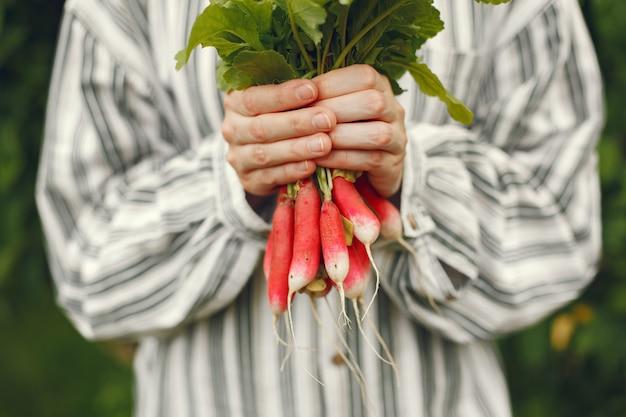 Femme au chapeau tenant des radis frais