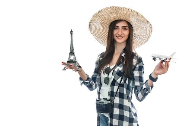 Femme au chapeau tenant la tour eiffel et avion isolé sur blanc