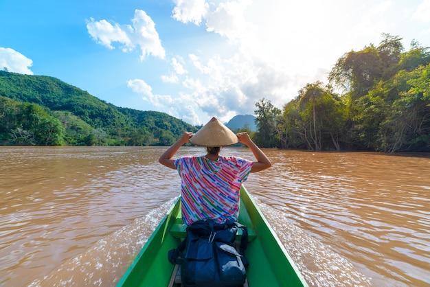 Femme au chapeau traditionnel qui navigue sur les eaux brunes de la rivière nam ou au laos